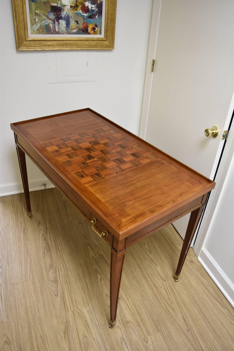 This unique Louis XVI Style Walnut Game Table features a reversible top.  The top has an inlaid checkerboard design on one side and felt on the reverse.  Underneath the removable top is a backgammon board.  The felt is in good condition with several