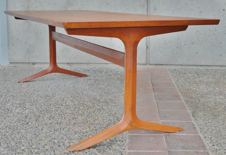 This stunning and rare Danish modern teak coffee table was designed by Peter Hvidt and Orla Mølgaard-Nielsen and is a rare example of their Silver Line series for France & Sons. The table features a gorgeous, sculptural teak clad aluminium base with