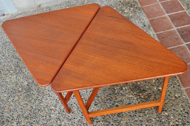 This totally fun pair of restored Danish modern teak folding tables are a clever design by Illum Wikkelsø. The tops are rounded triangles, and the legs fold out like a gate leg table with brass hinges, and a ball catch and stopper to hold them in