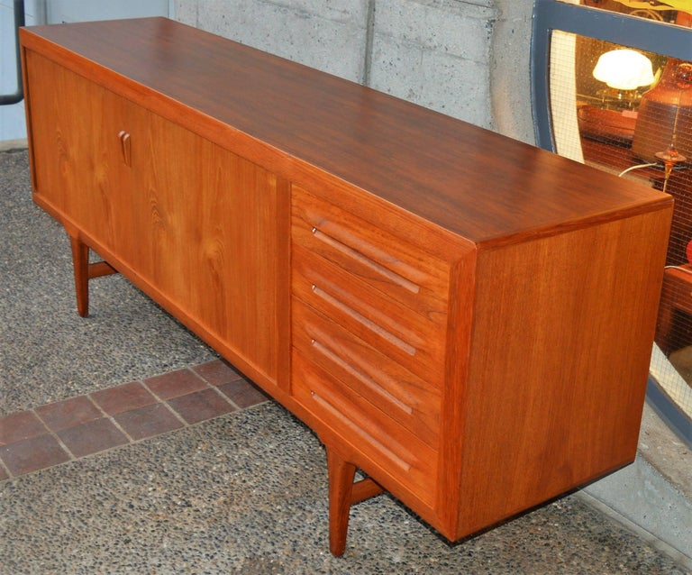 This absolutely impeccable, top quality Danish modern teak tambour credenza or buffet was designed by Ib Kofod Larsen in the 1950s. Featuring a mitred front edge molding detail that flares to meet the legs at the base, both on the front and back, an