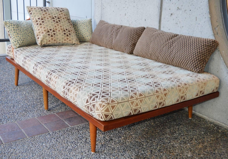 This lovely Danish Modern solid teak and oak daybed is perfect as a sofa, chaise or guest bed. Featuring a curved back spindle detail in oak at the head, this recently reupholstered lovely comes with all the throw pillows pictured, and the smaller