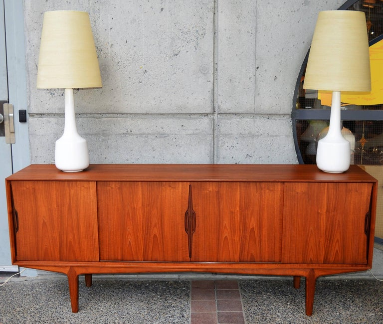 This stellar Danish teak buffet / credenza was designed by Knud Nielsen and has his iconic sculptural door pulls with a darker inside to really make them pop. Featuring clean, modern lines with crisp edges and a mitered front edge molding detail, as