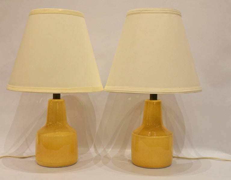 This lovely pair of soft yellow compact ceramic lamps were made by Lotte and Gunnar Bostlund and are the perfect size for compact bedside lamps. Paired with conical white/off-white lamp shades, though one has a spot that can be turned to the back.