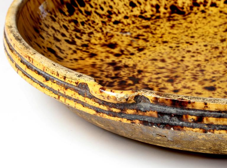 A large round antique terracotta cheese draining bowl with a gold and brown speckled glaze.