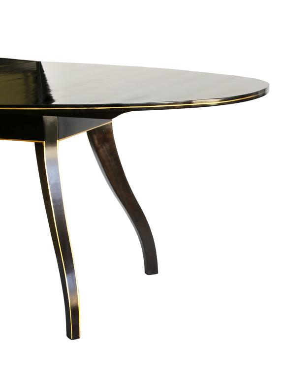 An extension dining table designed by Phoebe Howard in dark ebony stained wood. The table features Regency style spider legs with a painted 23-karat gilt banding detail on the edge of the leg and along the edge of the table. This table style is no
