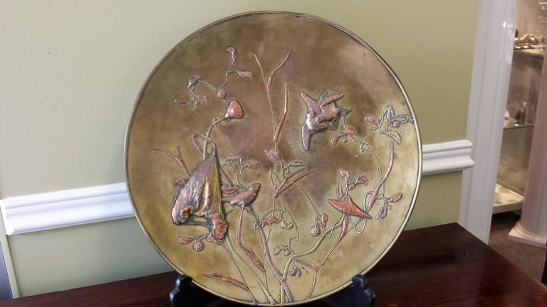 A large patinated bronze Japanese mixed metal overlay charger, Meiji Period (late 19th century), decorated in gold, silver, copper and bronze. Naturistically accurate depiction of sparrows, amongst, bamboo, berries and lotus pods.  The charger