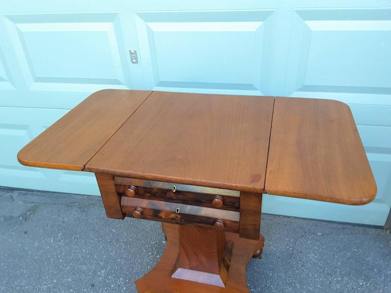 A neoclassical American Empire drop-leaf side table in mahogany, circa 1830-1840, Double front drawers with wood original knobs. The table is in flame mahogany and the secondary woods are in oak and pine. There are two drop leaves, when extended the