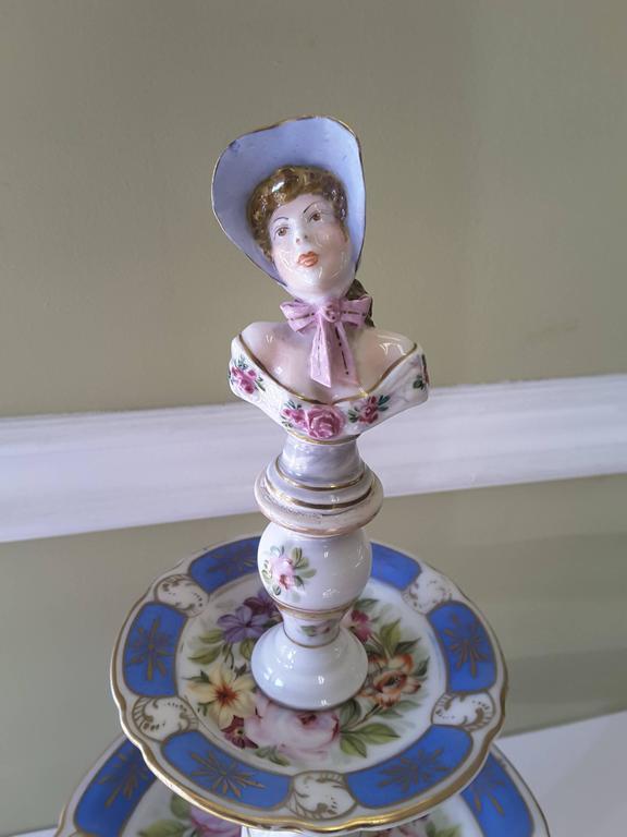 A rare Paris figural porcelain three-tier dessert Tazza, three graduated plates with floral decoration, gilt and