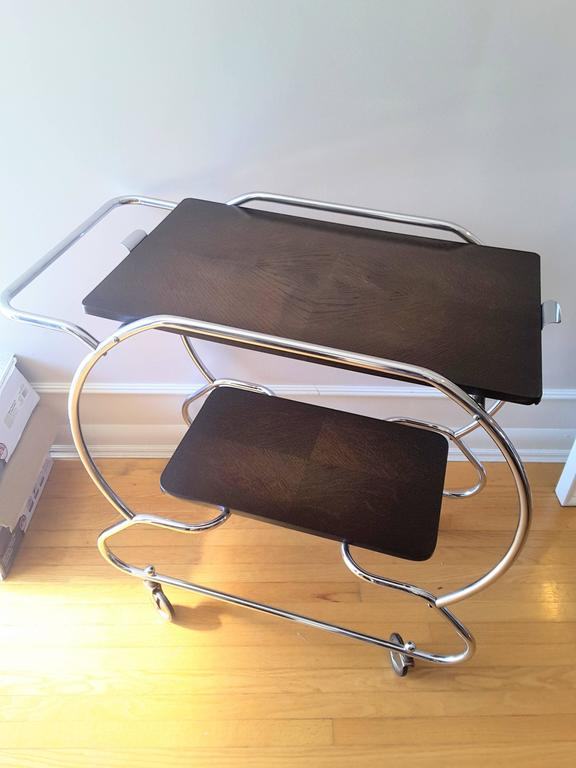 A Bauhaus vintage Art Deco bar cart, chromed nickel round tubing frame with Oak upper and lower shelf, both done in an oak geometric pattern. The upper shelf has handles and can be removed and used as a serving tray, with four bun feet on the