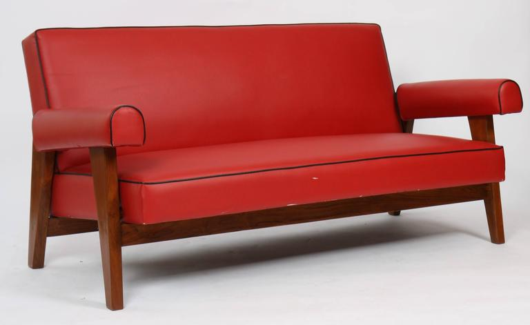Le Corbusier (1887-1965) - Pierre Jeanneret (1896-1967) Living room consisting of a sofa and two armchairs. Canapé in teak with flat sloping backrest, bridge lateral structure base. Detached Armrests with rounded cuffs. Seat, back and cuffs are