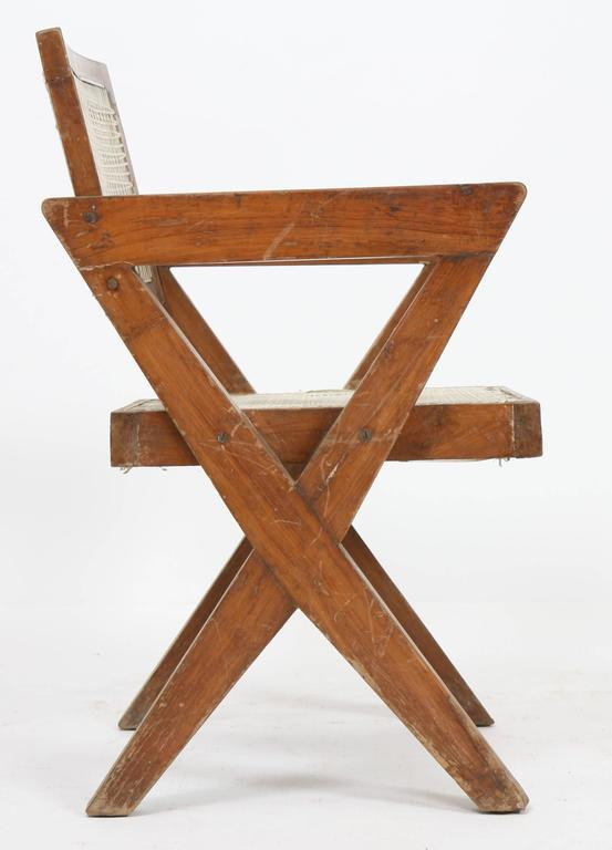 Pierre Jeanneret (1896-1967). Armchair in teak, with bended and slightly curved back. Detached armrests profiled on side compass feet. Cane seat and back, circa 1963-1964. Dimension: Height 82cm x Length 55cm x Depth approx. 50 cm. Origin: