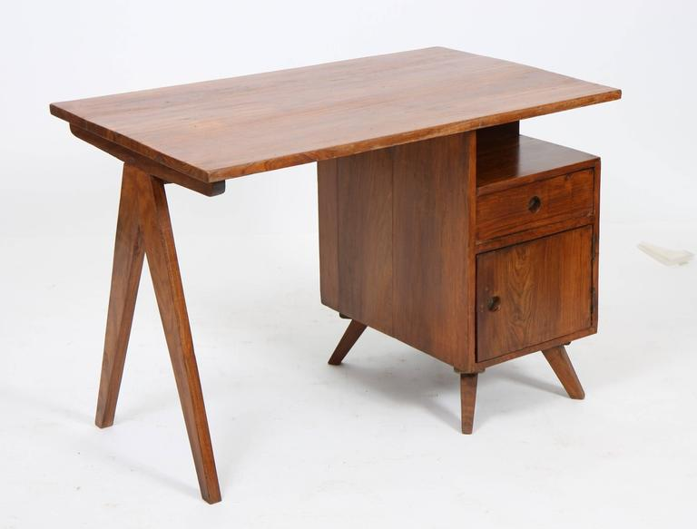 """Pierre Jeanneret (1896-1967). Small administrative desk, solid teak, tray mounted on """"V"""" leg on a trunk opening with a door and a drawer on the opposite side, circa 1960. Measures: Height 69 cm; length 99 cm; depth 61 cm. Provenance:"""