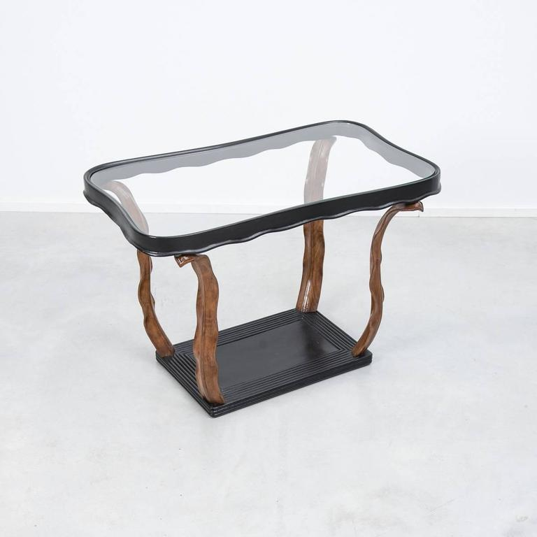 A refined side or coffee table designed by Milanese architect Paolo Buffa. The glass top is supported by a kidney shaped wood frame, which stands on four hand-carved wooden leaves. An exceptional piece of craftsmanship in the 1940s decorative
