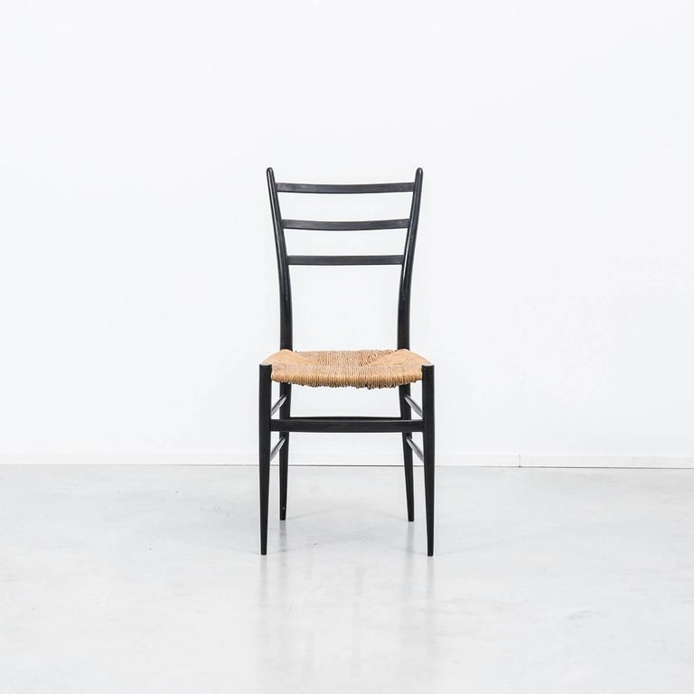 This set of 4 elegant Spinetto chairs have a very thin profile with black ebonized frames and wicker seats, manufactured in the 1950s by Chiavari, Italy. These chairs were the inspiration for Gio Ponti's famous Superleggera chair.