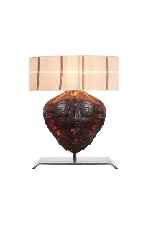 A rare pair of real antique turtle shell lamps on custom-made iron stands 20 cm x 54 cm converted into table lamps. Complete with lamp shades. Electrified. Three bulbs in each lamp, one in shade and two behind tortoiseshell to allow beautiful