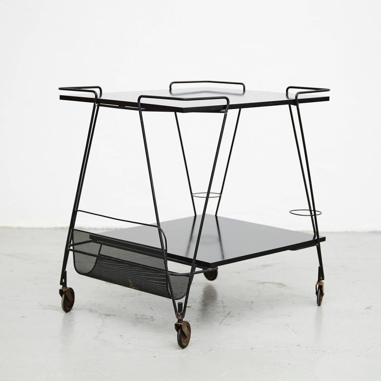 Trolley designed by Mathieu Matégot. Manufactured by Ateliers Matégot (France), circa 1950. Perforated metal lacquered in black and laminated wood.  In good original condition, with minor wear consistent with age and use, preserving a