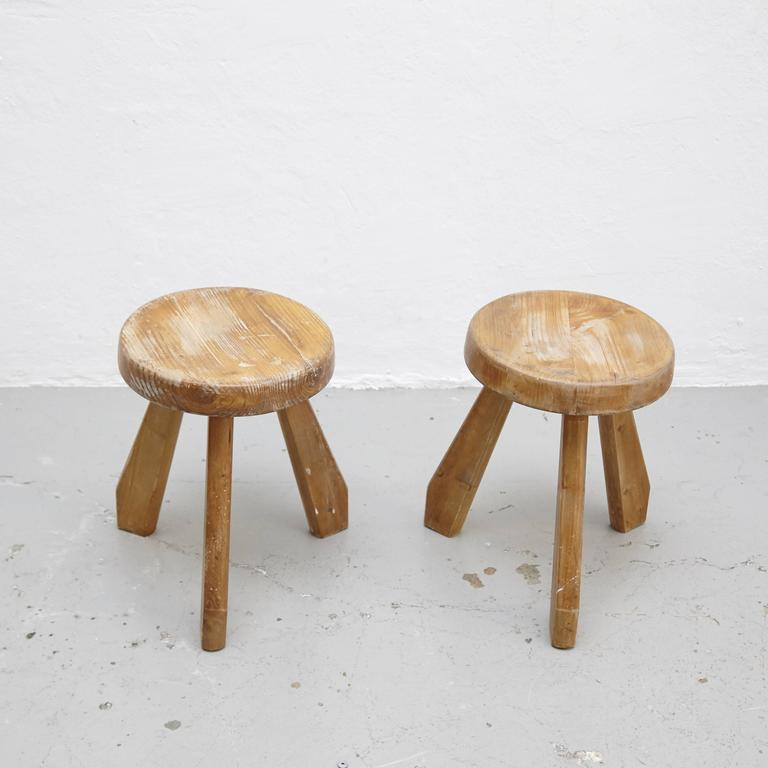 Stools, model Sandoz, designed by Charlotte Perriand, circa 1960. Manufactured in France. Pinewood.  In good original condition, with minor wear consistent with age and use, preserving a beautiful patina.  Charlotte Perriand (1903-1999). She