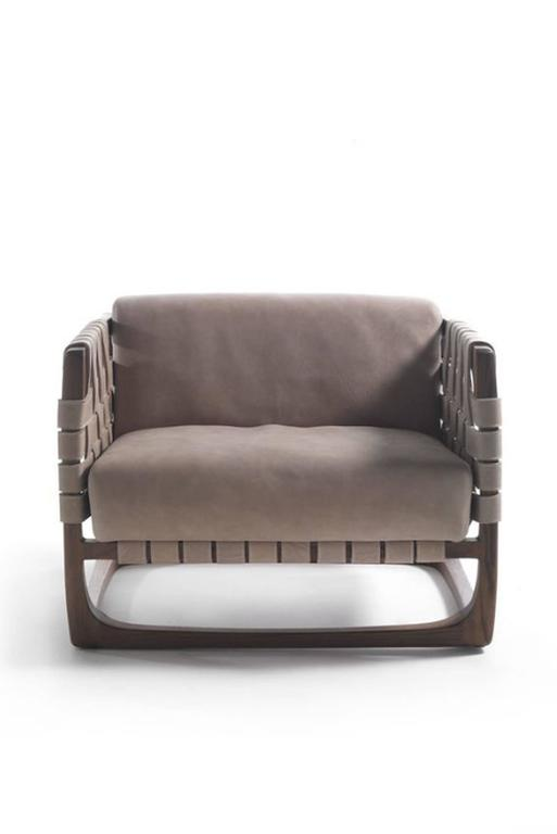 Armchair webbing padded seat in nubuck leather and frame in natural solid oak or walnut wood.