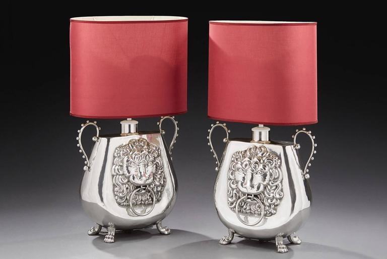 Lamp vase set of two with tin handles and four  ornate claw feet. Each faces with embossed lion heads. Vase: L 52 x H 51 cm. Vase with shade: H 99 cm. Unit price: 3450,00€.
