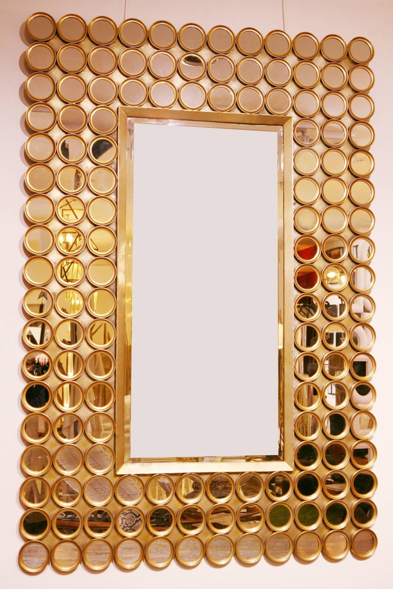 144 Facets mirror, with structure in mate gilded metal. With rectangular center mirror in bevelled mirror glass.
