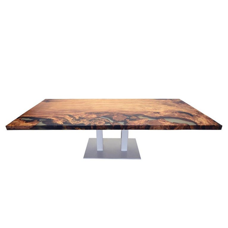 Dinning table Kauri wood with resin with solid Kauri wood top with mix of light and dark shades and with very strong patterns. With many high technology resin parts on one side of the top. With precatalyzed matt varnish finish. Steel threaded