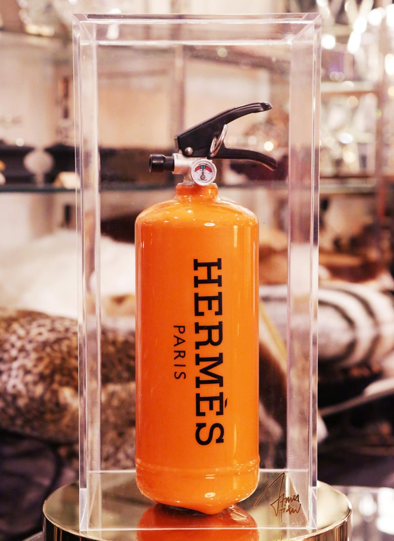 Extinguisher Hermes Paris.  Limited edition of 16 pieces. Exceptional piece.  Under plexiglass box. Measures: box: L 20 x D 20 x H 42.5cm. Extinguisher: L 10.5 x D 10.5 x H 35.5cm.