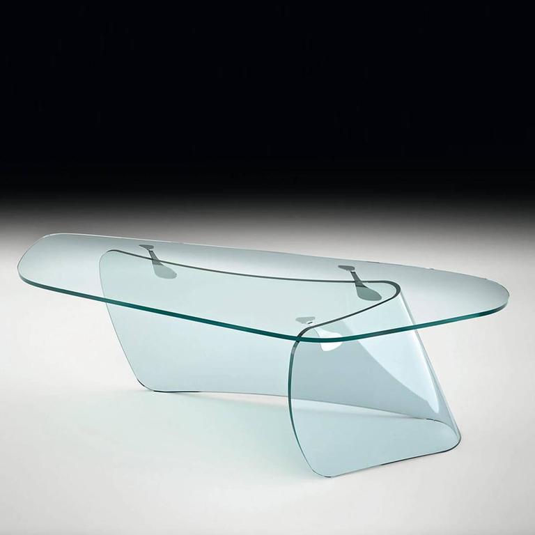 Desk Absolut composed of a curved transparent glass base 19mm and a clear glass top 15mm with fastening plates in  polished stainless steel. L220xP80xH74cm, price: € 8,600.00 L250xP91xH74cm, price: € 9,200.00 Pacific Compagnie collection.