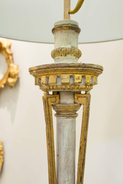 A carved giltwood and 'blanc de roi' painted Neoclassical Portuguese candlestick;  mounted as a table lamp.