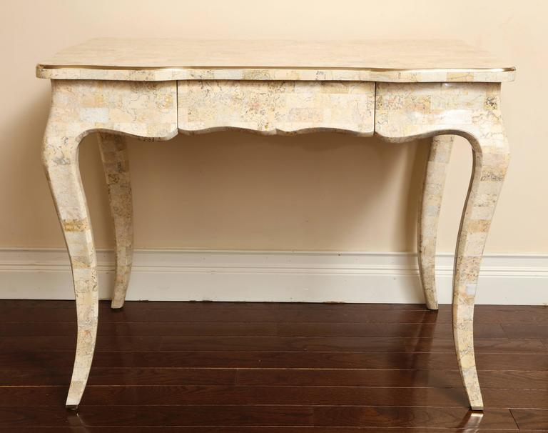 A Maitland Smith tesselated stone vintage desk with brass trim on the outer portion of the top. Of Rococo style; with scalloped apron and elegant cabriole legs terminating in brass sabots. There is a single drawer in the front with a signed brass