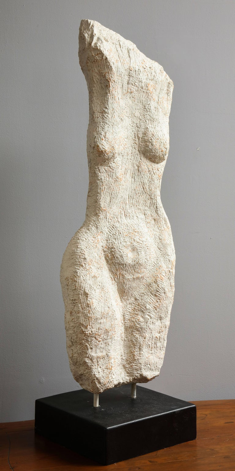 A modernist stone sculpture of a female nude torso, supported on a black painted stone plinth base.