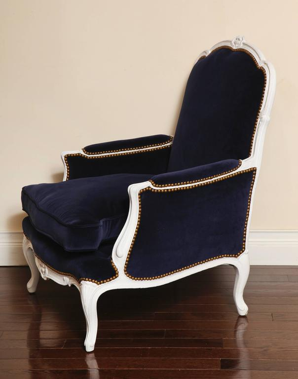 A beautifully proportioned French Louis XV style 19th century painted white bergère. The frame with cabriole legs and nicely carved cartouches on the crest and seat rail. The chair is newly upholstered in a rich dark blue velvet with antique brass
