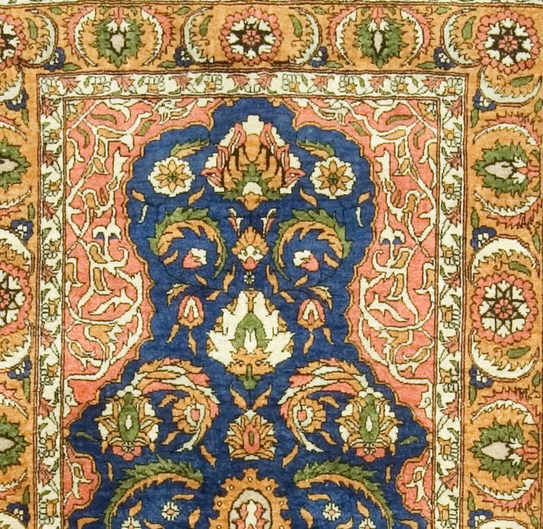 This fine silk Hereke rug bearing the Hereke mark is an artistic interpretation of early 17th century Ottoman Turkish court rugs. The blue mihrab with palmettes and curving Saz leaves and the quarter medallions at the lower corners is in a Classic
