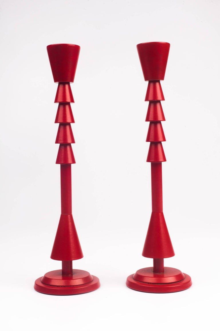 Prototype pair of candlesticks Ad Arte by Ugo La Pietra, made in Italy in 1985. Bright red color with combination of geometric forms. Delicate, small stature, taking slender taper candles 1/2 inch base.   UGO LA PIETRA was a main figure in the