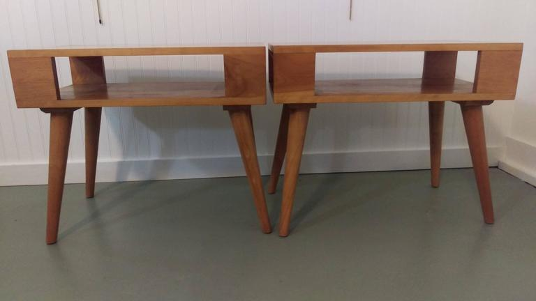 Versatile pair of modernist and architectural form end tables or nightstands. Designed by Russel Wright for Conant Ball International. Constructed in solid maple, in its original condition shows minor wear consistent with age and use.