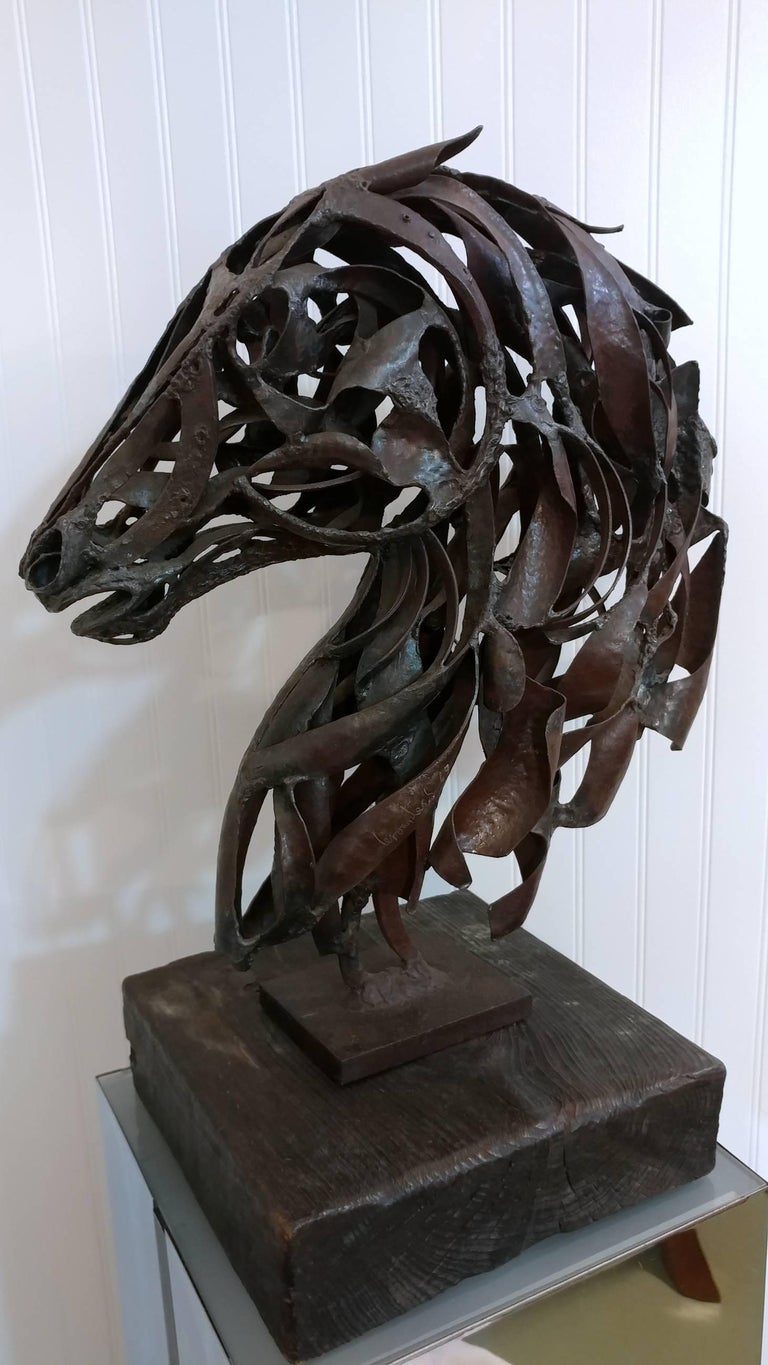 An early work by artist Pedro Miguel de Cervantes Salvadores. Since childhood he has been fascinaed by horses. This horse bust sculpture is a fine example and displays lively energy from any angle, masterfully crafted in wrought iron on solid wood