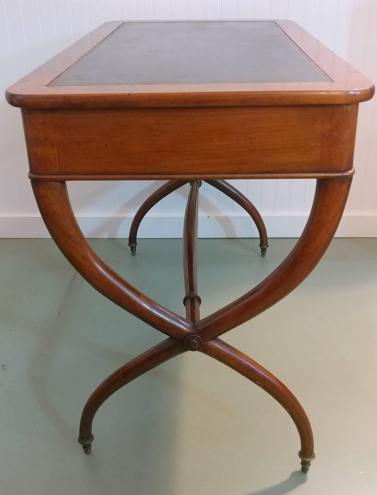 Lovely French early 1900s mahogany writing desk, has a stylish curvaceous X-base joined by a turned stretcher, tooled leather top surface, accents with all original brass ring pulls and capped at feet. In exceptional original condition for its age,