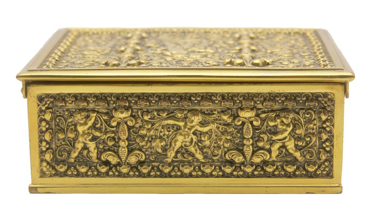 The top, front, sides and back are beautifully cast in gilt brass and feature panels