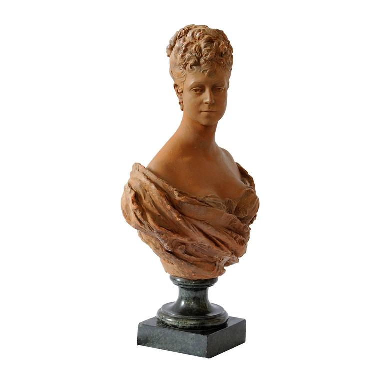 This is a rather beautiful French mid-19th century terracotta bust of a young 18th century noble woman standing on a green marble base, circa 1860.