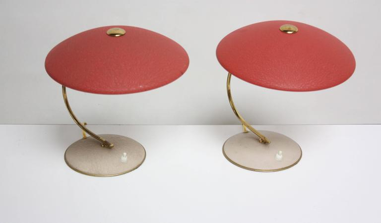 These Dutch brass table lamps are comprised of light maroon adjustable shades and beige metal bases. The paint is original to the lamps and shows minor loss or wear loss. The sockets are different on each lamp (as found) but will facilitate the same