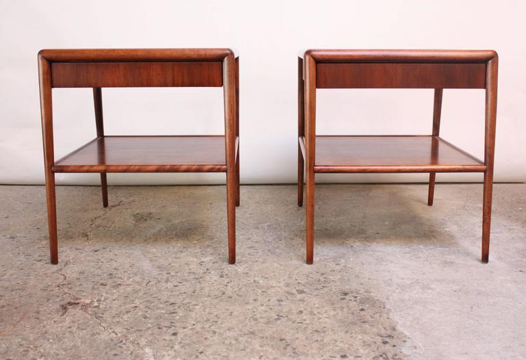 These scarce walnut end tables were designed by Robsjohn-Gibbings for Widdicomb in the 1950s and feature two tiers and a single drawer. Superior craftsmanship and clean, minimal design. Both end tables retain the Widdicomb / T.H. Robsjohn-Gibbings