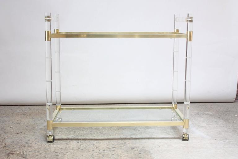Two-tiered serving or bar cart designed in the 1960s by Charles Hollis Jones for his 'Regency Bamboo' line featuring a brass frame that has been hand-polished to a perfect, satin finish with faux-bamboo lucite rails. The beveled glass surfaces