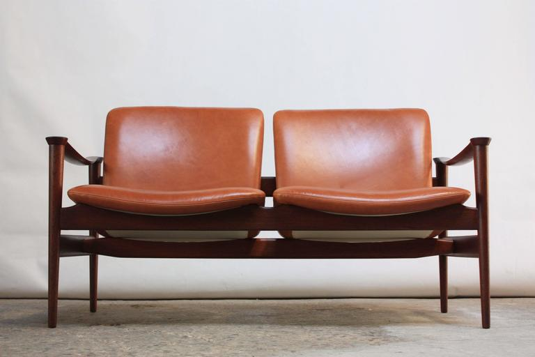 This two-seat sofa was designed by Fredrik Kayser for Vatne Lenestolfabrikk (Norway) in the 1960s. Magnificent frame in sculpted teak with armrests that best resemble two conjoined cul-de-sacs. Solid patinated brass posts connect the seats to the