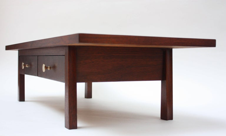 Elegant jewelry chest composed of two small drawers with brass pulls below a sweeping walnut surface. Sculptural legs have a slight taper at the top and expand out at the end. At 33