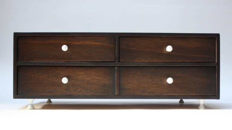 Originally designed in the 1950s by American of Martinsville as the smaller 'chest-on-chest' component to sit atop the corresponding sideboard, this piece can be used to hold smaller linens, napkin rings, and silverware. However, its more practical,