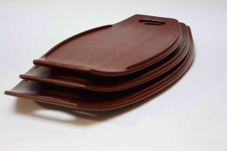 Complete set of three staved teak serving trays by Jens Quistgaard for Dansk. Designed with a slight size disparity (small, medium, and large) to allow the trays to nest together when not in use. Early examples, as indicated by the stamp to the