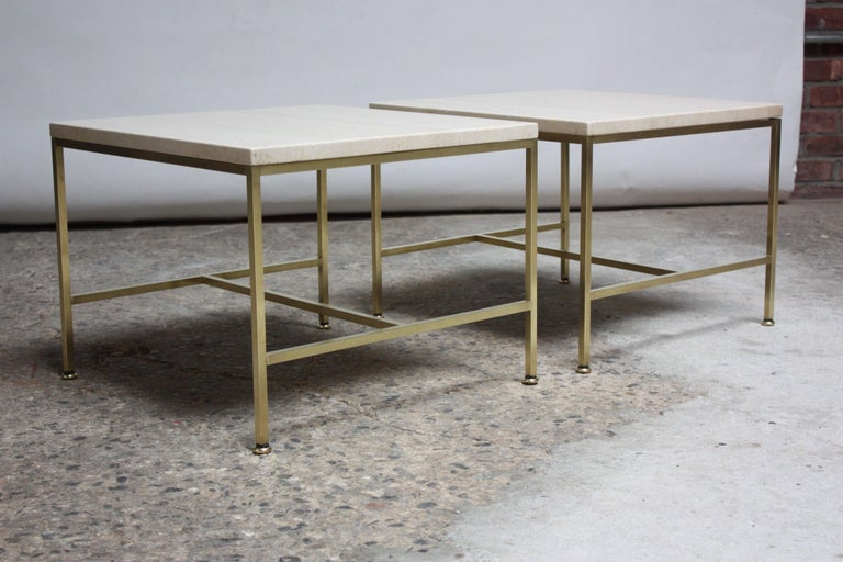 Pair of 1950s Paul McCobb for Directional side / occasional tables composed of tubular brass frames / brass feet and square, travertine tops. Brass is in beautiful, polished condition; showing only minor wear (light spots remain post-buff and polish