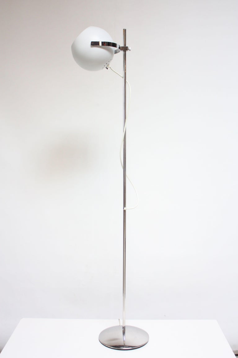 1960s Reggiani floor lamp composed of a single fixture that can be raised / lowered roughly 3/4 of the way up / down the stem (the cord exit point on the stem is lowest point of adjustability). Additionally, the fixture has full 360 flexibility with