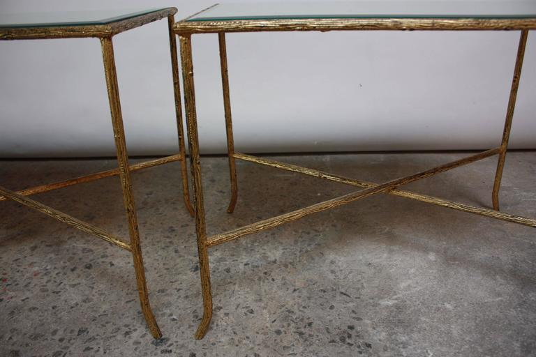 These Italian end tables are comprised of a heavily textured gilded-steel X-base frame and beveled mirror inserts. There is one scratch to one of the mirror tops, but otherwise these tables are in excellent, vintage condition.