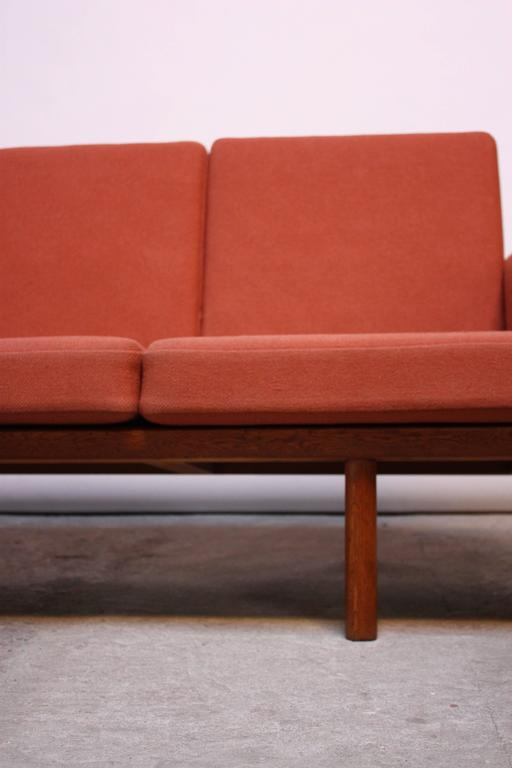 This four-seater sofa (model GE 236/4) was designed by Hans Wegner for GETAMA in the 1950s and is comprised of a solid oak slatted-back frame. The cushions, marked 'Ryghynde' are original to the piece and are a coral/peach wool. The GETAMA branding