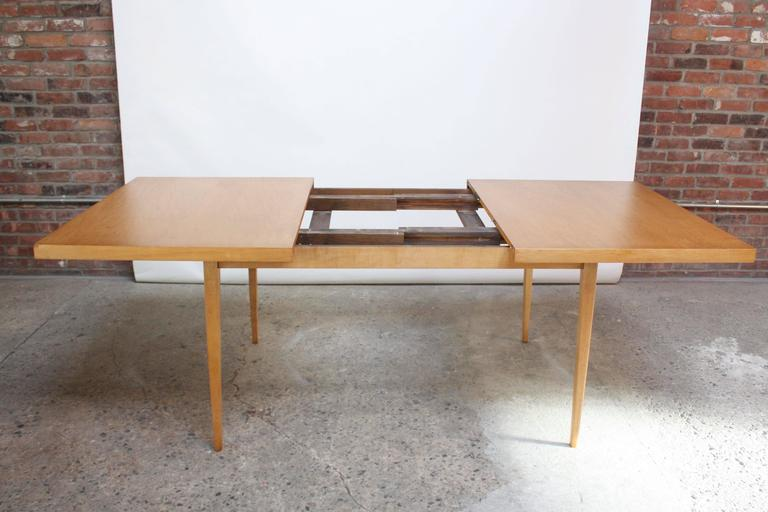 "This minimal maple dining table was designed in the 1950s by Paul McCobb as part of his 'Planner Group' for the Winchendon Furniture Company. The table without leaves is 60"" L. Each leaf is 12"" L, and the total length when fully extended is 84""."